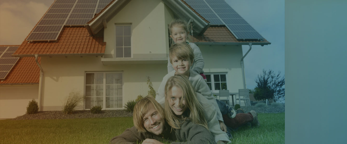 Family of 4 sitting in front of a house that has solar panels